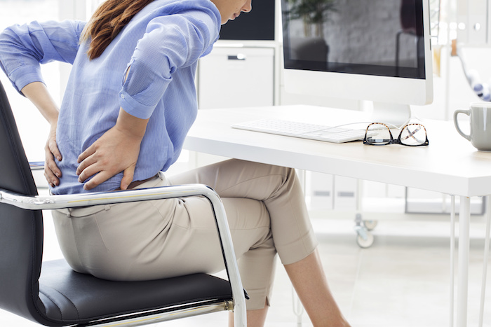 Businesswoman with pain in back; Blog: Back Pain Symptoms You Shouldn't Ignore