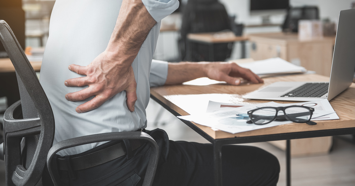 Employer having pain in back. He holding it by hand while sitting at table during job. Worker with bad state of health concept; blog: prevent back pain at work