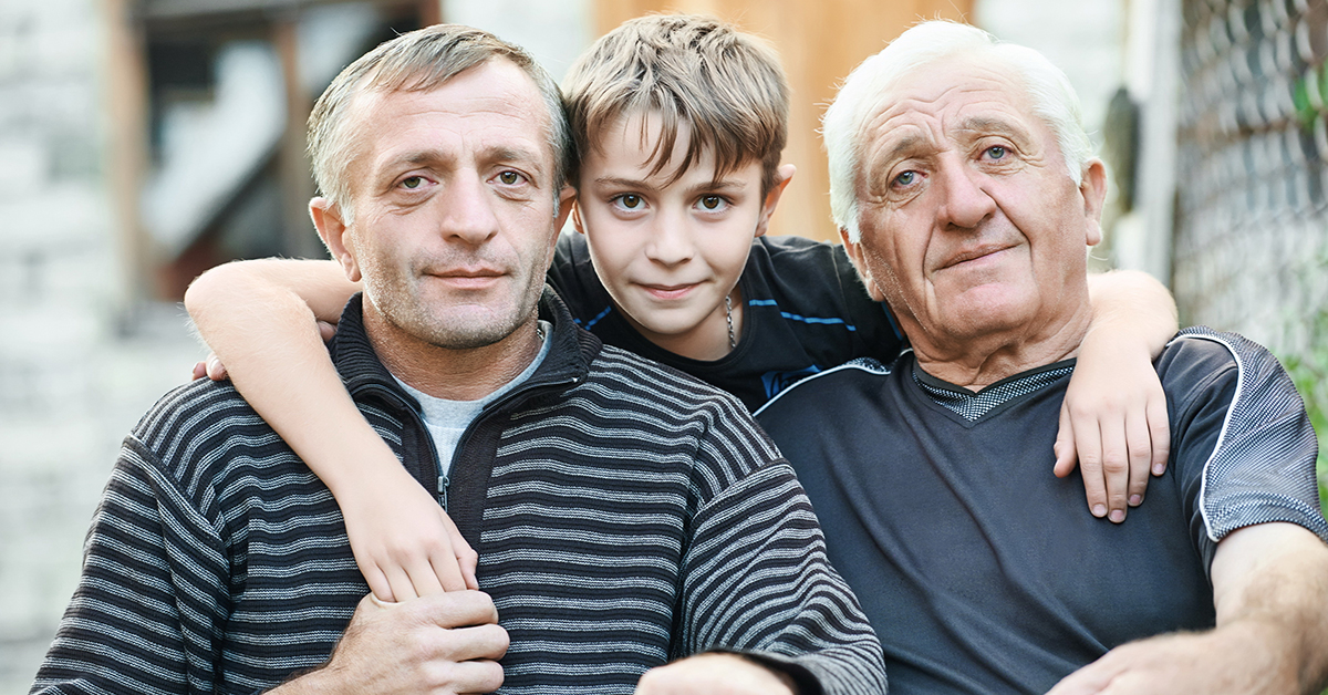 Multi generation portrait of happy grandfather with his son and grandson sitting in front of the country house; blog: Is Degenerative Disc Disease Genetic?