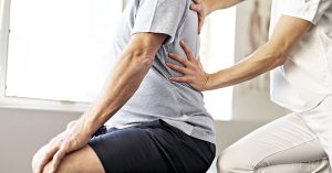 Modern rehabilitation physiotherapy worker with senior client; blog: What to Expect After Minimally Invasive Back Surgery