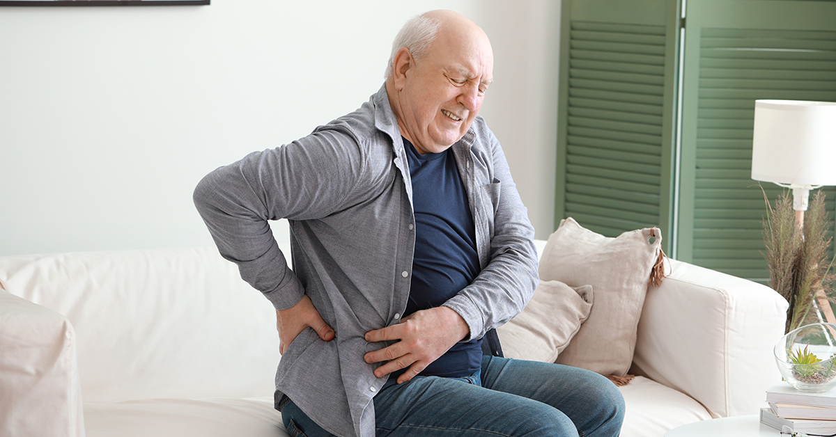 Senior man suffering from back pain at home; blog: Does Cold Weather Cause Back Pain?
