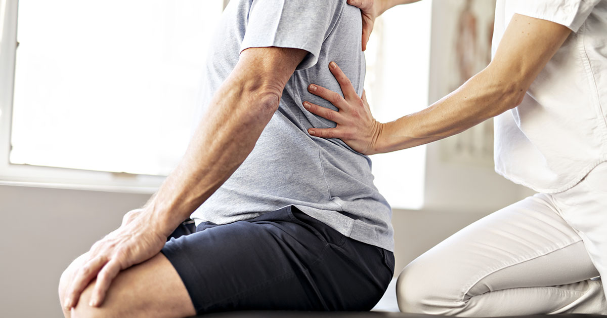 Modern rehabilitation physiotherapy worker with senior client; blog: Will I Need Physical Therapy After Back Surgery?