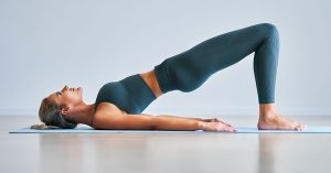 Picture of adult woman practising yoga at home; blog: 7 Exercises for Lower Back Pain Relief