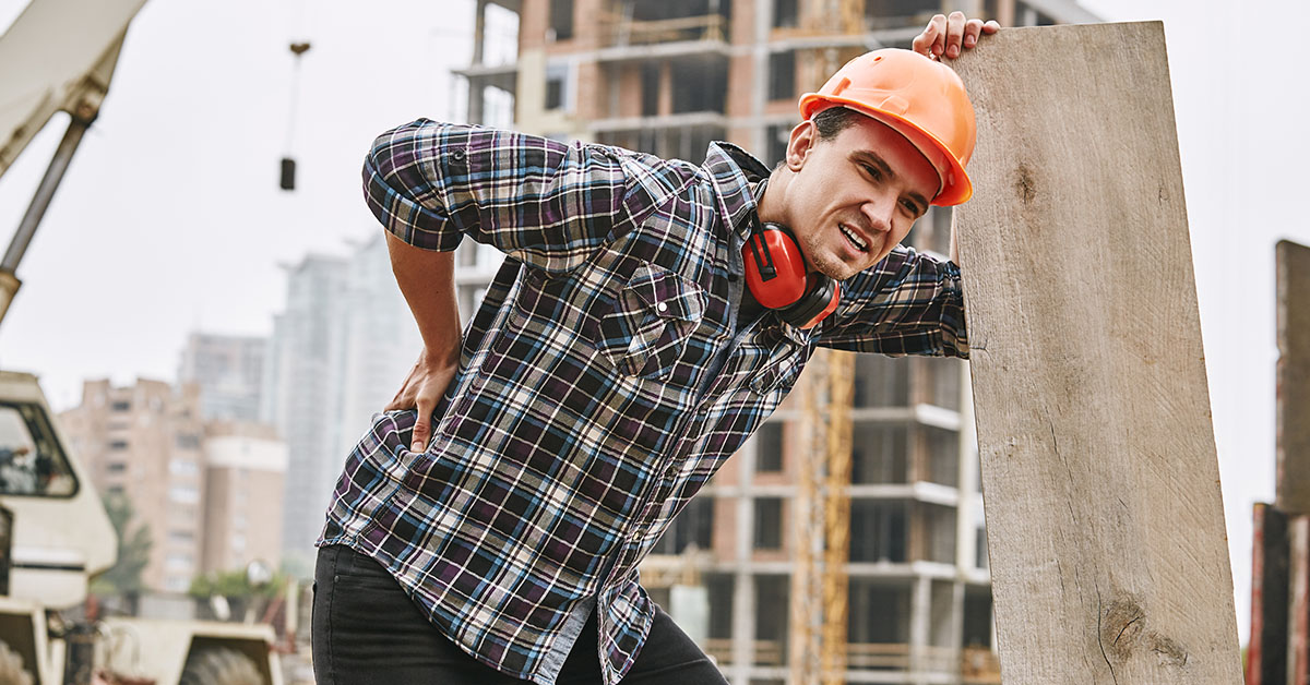 Hard work. Construction worker in protective helmet feeling back pain while working at construction site. Building construction. Pain concept. Dangerous job; blog: Top 10 Jobs That Cause Back Pain